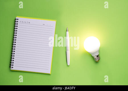 Note book and light bulb on green background. - Stock Photo