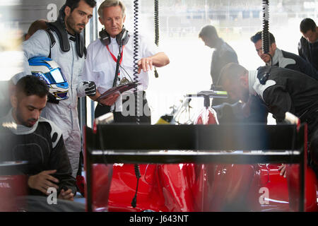 Manager and formula one driver watching pit crew working on race car in repair garage - Stock Photo