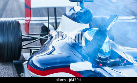 Formula one race car driver cheering with fist crossing finish line on sports track - Stock Photo
