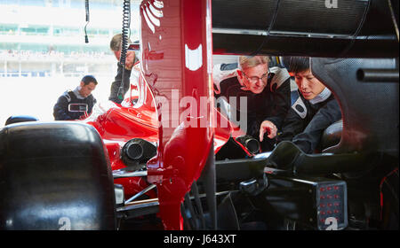 Pit crew mechanics examining race car in repair garage - Stock Photo