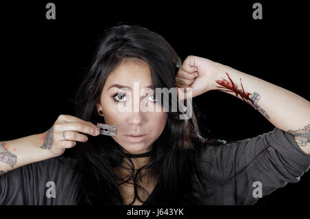 Quito, Ecuador - May 09, 2017: Sad teenager with her arm injuried by a gillette, bue whale challenge, social suicide - Stock Photo