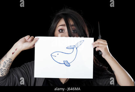 Quito, Ecuador - May 09, 2017: Anxious teenager drawing a whale over a sheet of paper, social suicide concept as - Stock Photo