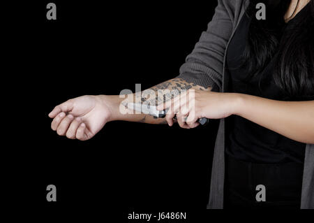 Quito, Ecuador - May 09, 2017: Close up of a woman cutting her arm with a knife, social suicide concept as a sociology - Stock Photo