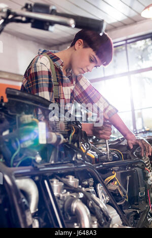 Female motorcycle mechanic repairing motorcycle in workshop - Stock Photo