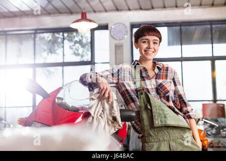 Portrait confident female motorcycle mechanic in workshop - Stock Photo