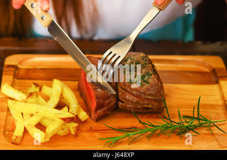 delicious succulent grilled meat on wooden table using kitchen utensils - Stock Photo