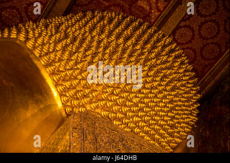Abstract view of golden texture of the head of a large reclining Buddha in Bangkok, Thailand - Stock Photo