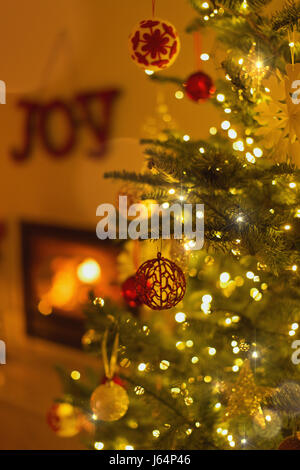 Ornaments hanging from Christmas tree with string lights in living room - Stock Photo