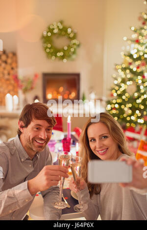 Smiling couple drinking champagne and taking selfie at Christmas dinner table - Stock Photo