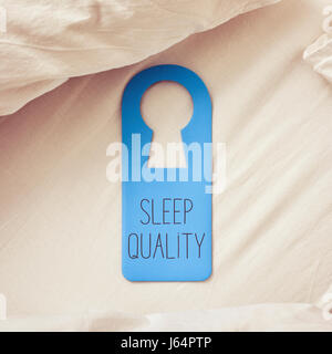 closeup of a blue door hanger with the text sleep quality written in it, placed on a comfortable bed - Stock Photo