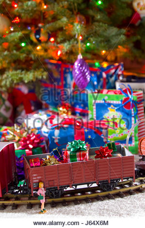 Toy electronic train on track in front of decorated Christmas tree with many wrapped presents piled beneath it. - Stock Photo