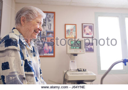 Elderly Caucasian woman sitting on examination bed in a doctor's office, Honolulu, Oahu, Hawaii, USA - Stock Photo