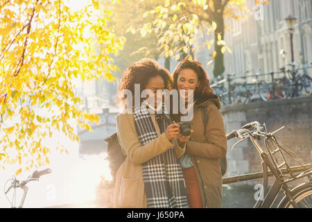 Smiling young women friends with digital camera along sunny urban autumn canal, Amsterdam - Stock Photo