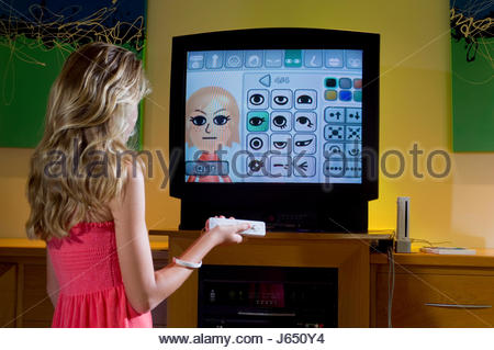 Teenage girl with blonde hair creating a personal avatar using a Nintendo Wii console and a hand held infrared game - Stock Photo