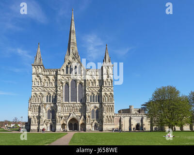 Salisbury Cathedral west front and close with people relaxing in the sun - Stock Photo