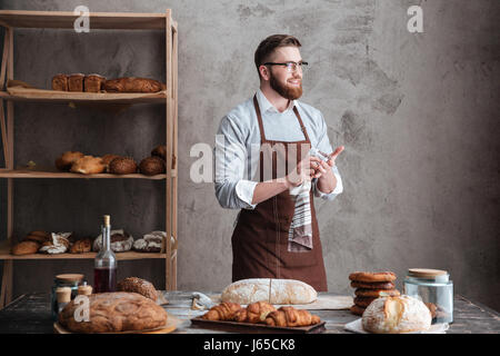 Picture of young happy bearded man wearing glasses baker standing near a lot of bread. Looking aside. - Stock Photo