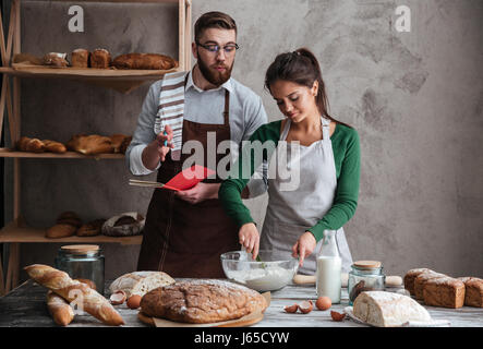 Young smiling woman under sensitive guidance of her man listening recipe of bread and cooking it in kitchen - Stock Photo