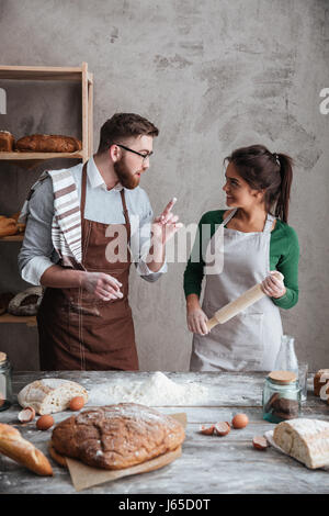 Bearded man in apron tellinh his woman with polling pin how to bake bread - Stock Photo