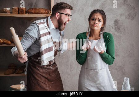 Angry bearded man in glasses shouting at his woan in apron while they cooking in kitchen - Stock Photo