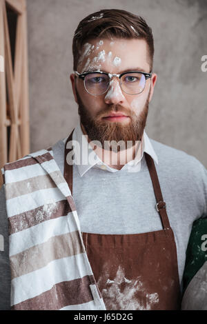 Portrait of bearded man in glasses and apron whose face stained with flour - Stock Photo