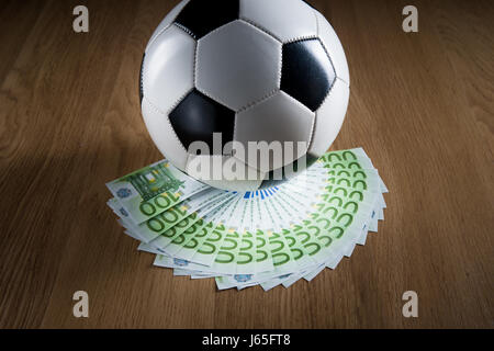 Soccer ball with fan of euro banknotes on hardwood floor. - Stock Photo