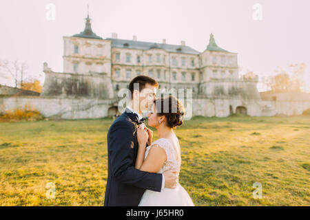 The horizontal side portrait of the happy newlyweds at the background of the old palace. The groom is kissing the - Stock Photo