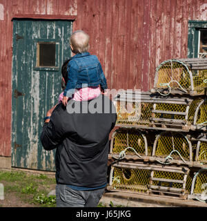Father holding toddler on shoulder at fishing shed, North Rustico, Prince Edward Island, Canada - Stock Photo