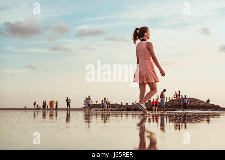 A beautiful girl walks along the beach at low tide. Her reflection mirrors off the wet sand. Tourists in the background - Stock Photo