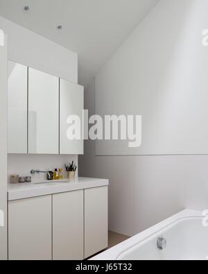 Mirrored cabinets above basin in pure white bathroom - Stock Photo