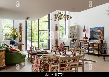 Triple-height living space with  rare wooden Austrian columns, books and old textiles - Stock Photo