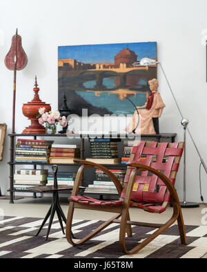 Collection of books on iron table with 1930s painting of river Tiber - Stock Photo