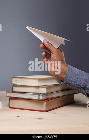 Conceptual image, Paper Aeroplane in the hand and on the books. - Stock Photo