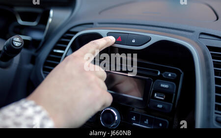 Male hand pressing emergency warning button on car console, closeup - Stock Photo