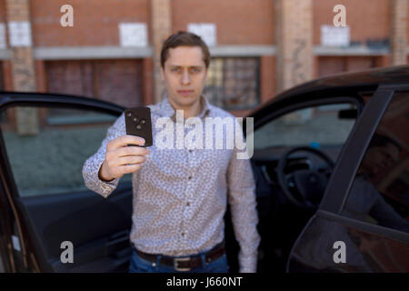 young owner man standing near a car and holding a car alarm key. Man blur effect. - Stock Photo