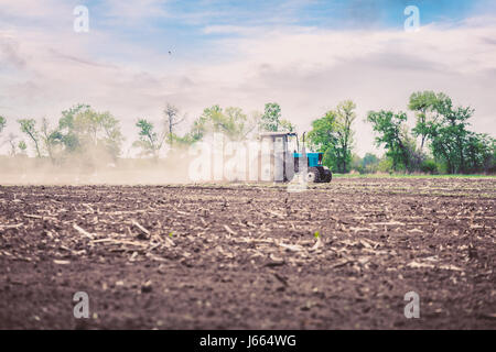 Tractor plows a field in the spring against a beautiful sunset sky - Stock Photo