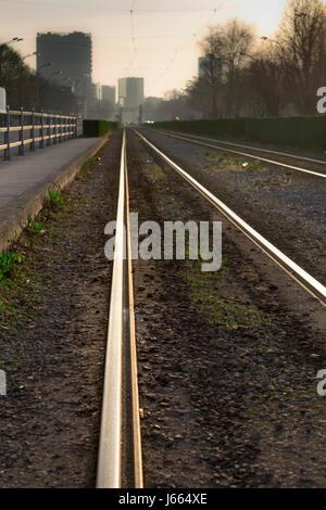 Empty tram rails at sunrise - Stock Photo