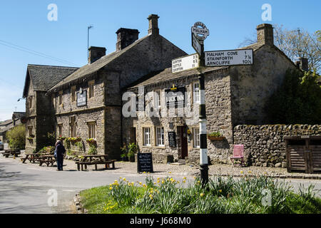 The Buck Inn hikers bar in village pub and old road sign in spring. Malham, Malhamdale, Yorkshire Dales National - Stock Photo