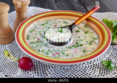 Vegetarian cold soup made of vegetables: potato, radish, dill, cucumber, with yogurt in a ceramic bowl. Traditional - Stock Photo