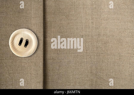 Wooden button with black thread on canvas background - Stock Photo