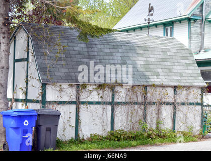An old barn with modern recycle bins in front surrounded by trees.  Even country folk are recycling now - Stock Photo