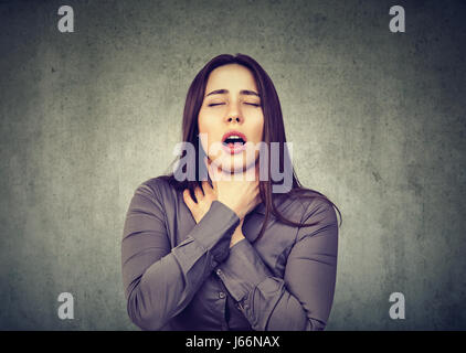 Young woman having asthma attack or choking can't breath suffering from respiration problems isolated on gray background - Stock Photo