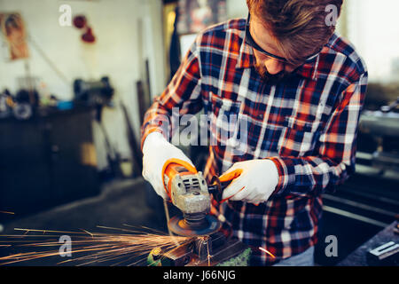 Young manual worker working with grinder - Stock Photo