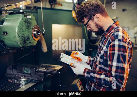 Young mechanic checks list - Stock Photo