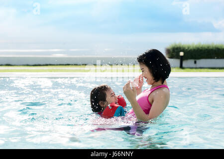 Happy Asian mother and daughter having fun in hotel swimming pool near sea enjoying summer vacation. Asian family - Stock Photo