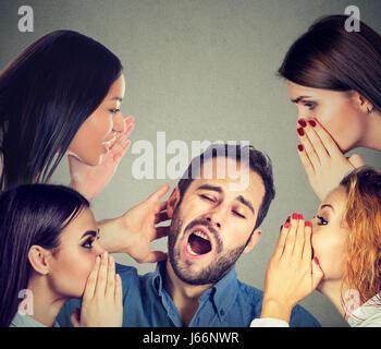 Four women whispering a secret latest gossip to a bored sleepy man - Stock Photo