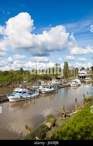 Commercial fishing boats tied up in a narrow tidal channel - Stock Photo