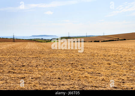 View across a harvested stubble crop field, the Isle of Portland in the distance, Dorset, UK - Stock Photo