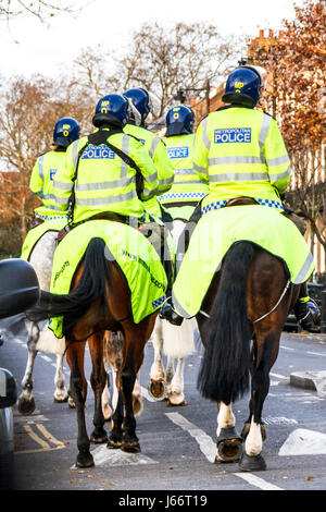 Mounted police officers in yellow high-visibility uniform on match day, Islington, London, UK - Stock Photo