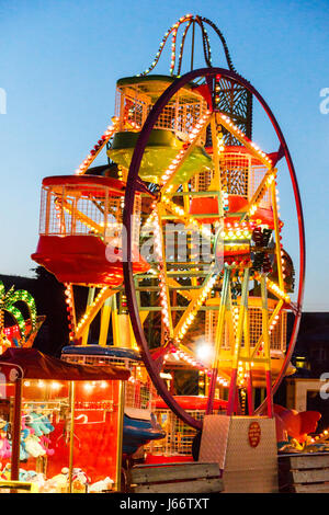 A brightly-lit children's Ferris wheel  at evening time on the promenade at Bowleaze Cove, Dorset, England, UK - Stock Photo