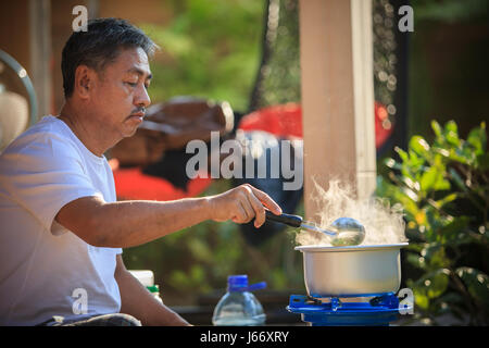old man cooking morning food meal in hot pot on lpg gas stove - Stock Photo